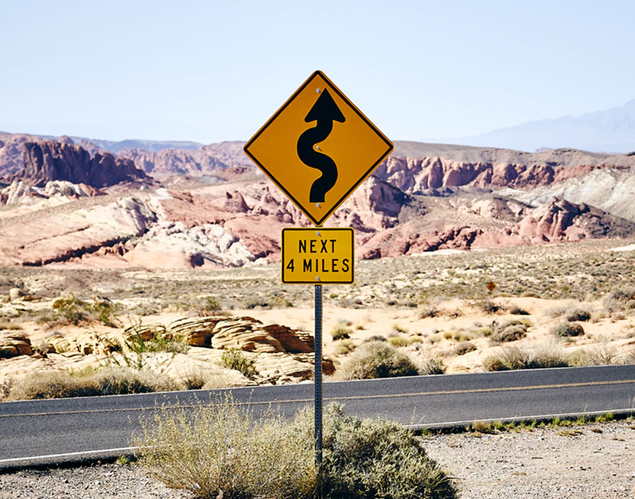 Road sign near a highway in Nevada with backdrop of natural rock formations
